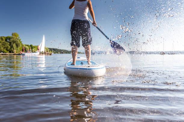 standup-paddling an einem schönen see - stehpaddeln stock-fotos und bilder