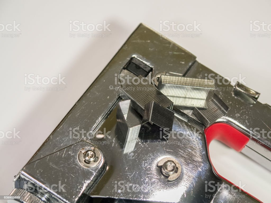 Staple gun and staples on white isolated background closeup stock photo