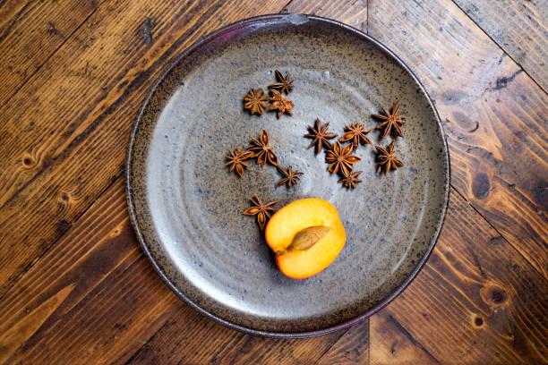 sternanis und eine halbe pfirsich auf rustikale teller stillleben - steingut geschirr stock-fotos und bilder