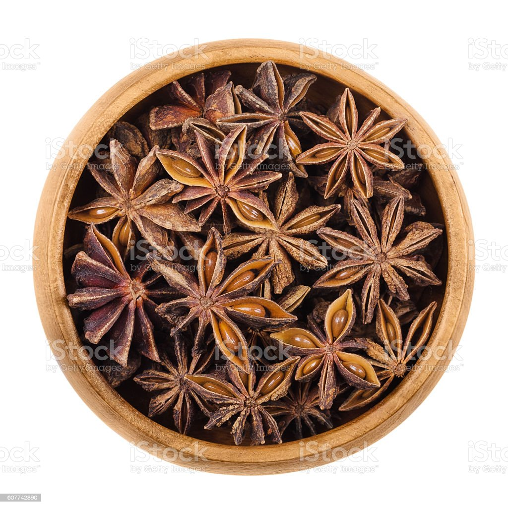 Star anise seeds in a wooden bowl over white stock photo