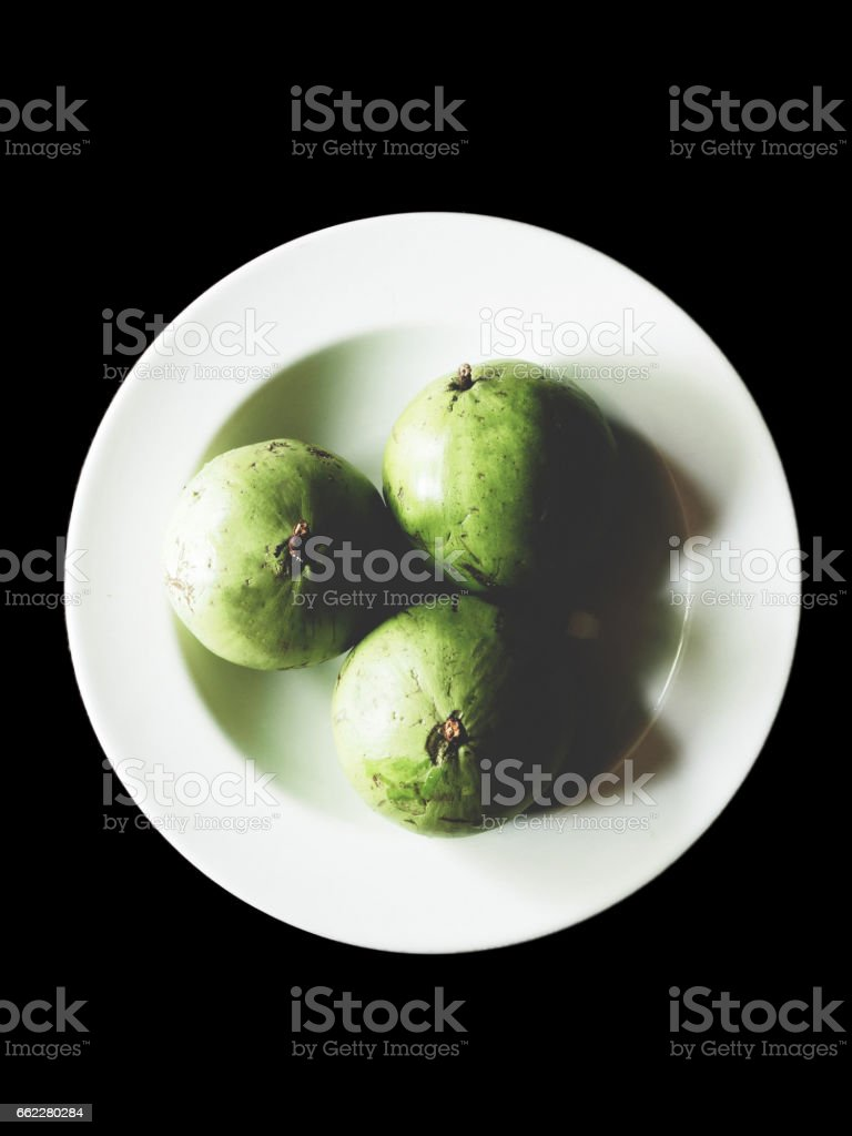 Star apple on the white dish - black isolated royalty-free stock photo