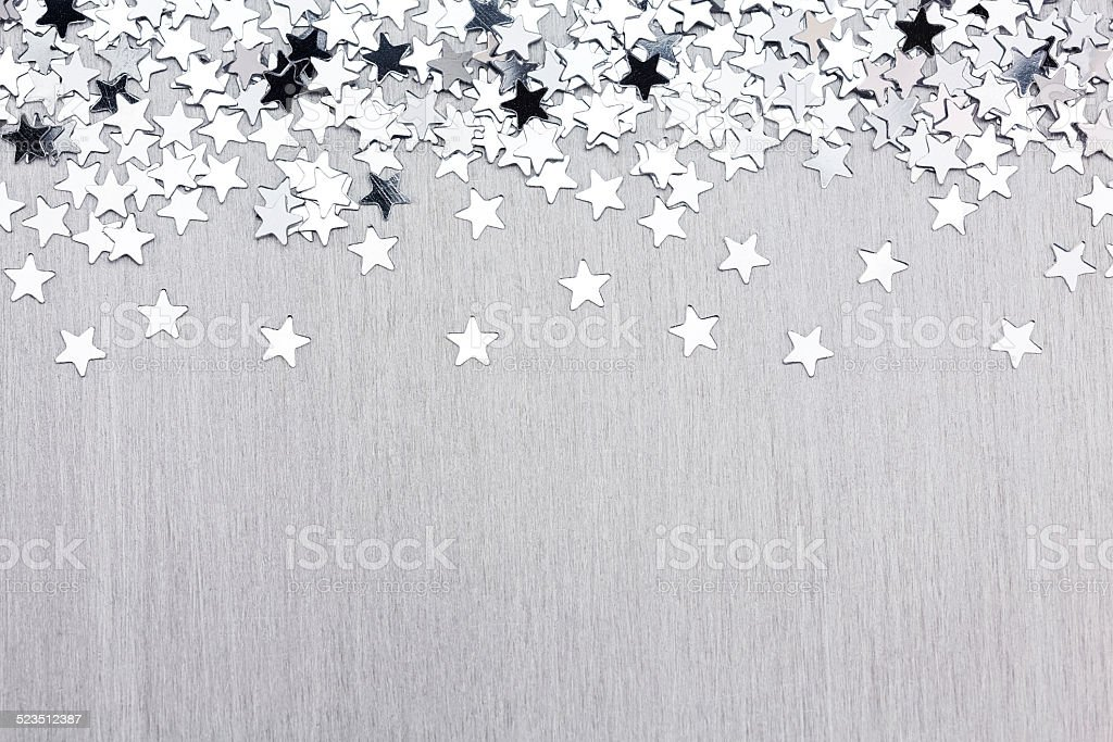 Star confetti on silver metal background stock photo