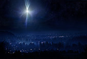 A conceptual photo montage, meant to represent the town of Bethlehem and the Christmas star in the night sky the evening that Christ was born. Horizontal with copy space.