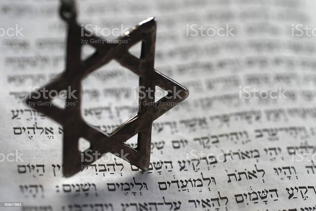 Star of David keychain on top of Old Testament book stock photo
