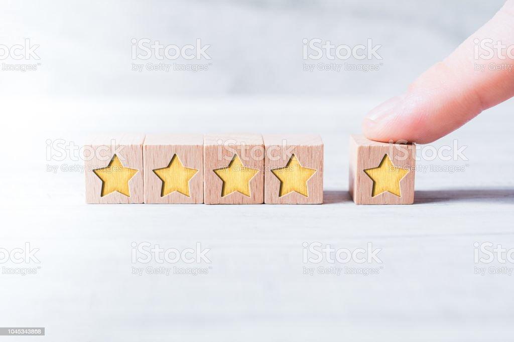 5-Sterne-Ranking durch hölzerne Blöcke gebildet und durch einen männlichen Finger auf einem weißen Tisch angeordnet - Lizenzfrei Qualität Stock-Foto