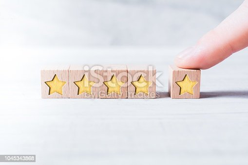 5 Star Ranking Formed By Wooden Blocks And Arranged By A Male Finger On White Table