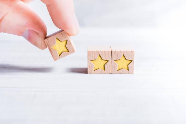 木製のブロックによって形成され、白いテーブルの上に男性の指によって配置された3つ星ランキング - 星 ストックフォトと画像