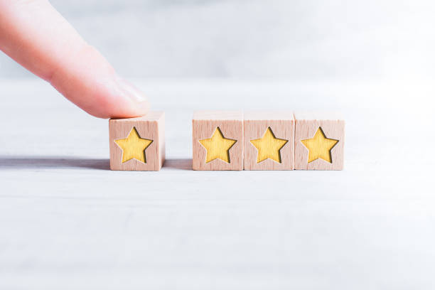 4 Star Rating Formed By Wooden Blocks And Arranged By A Male Finger On A White Table stock photo
