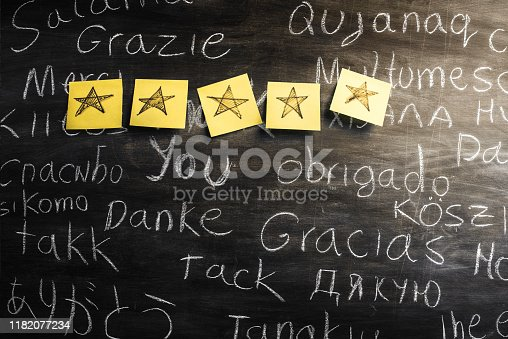 Thank You in many languages written with chalk on blackboard. There are 5 stars drawn on adhesive notes attached to the blackboard. Customer satisfaction concept