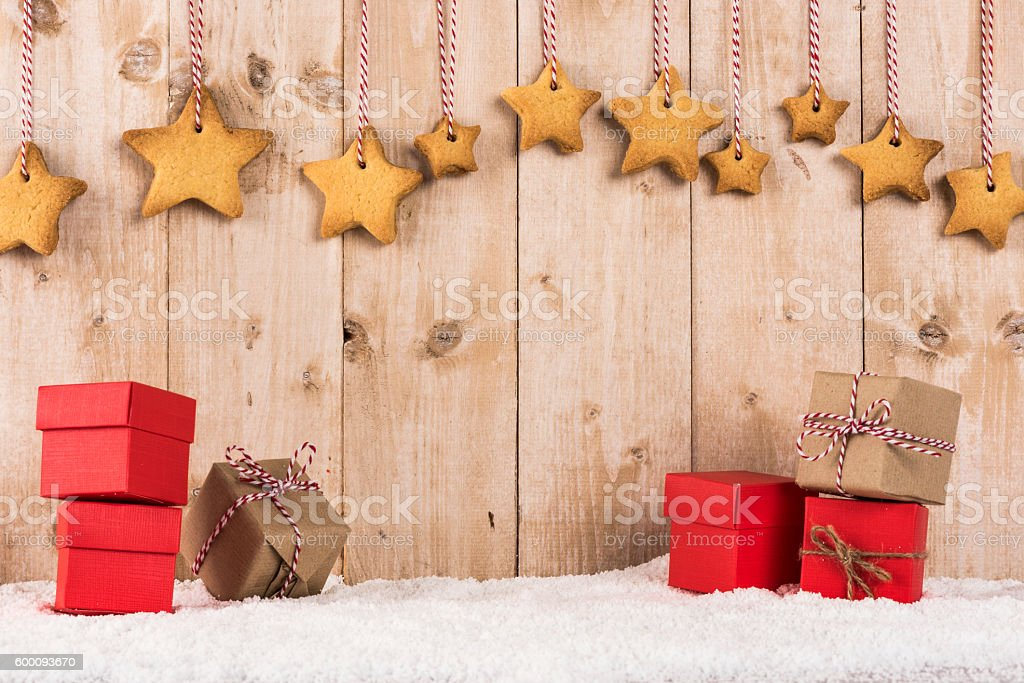 Star shape biscuits hanging over presents Star shape biscuits hanging from white and red thread in front of wooden background over presents Backgrounds Stock Photo
