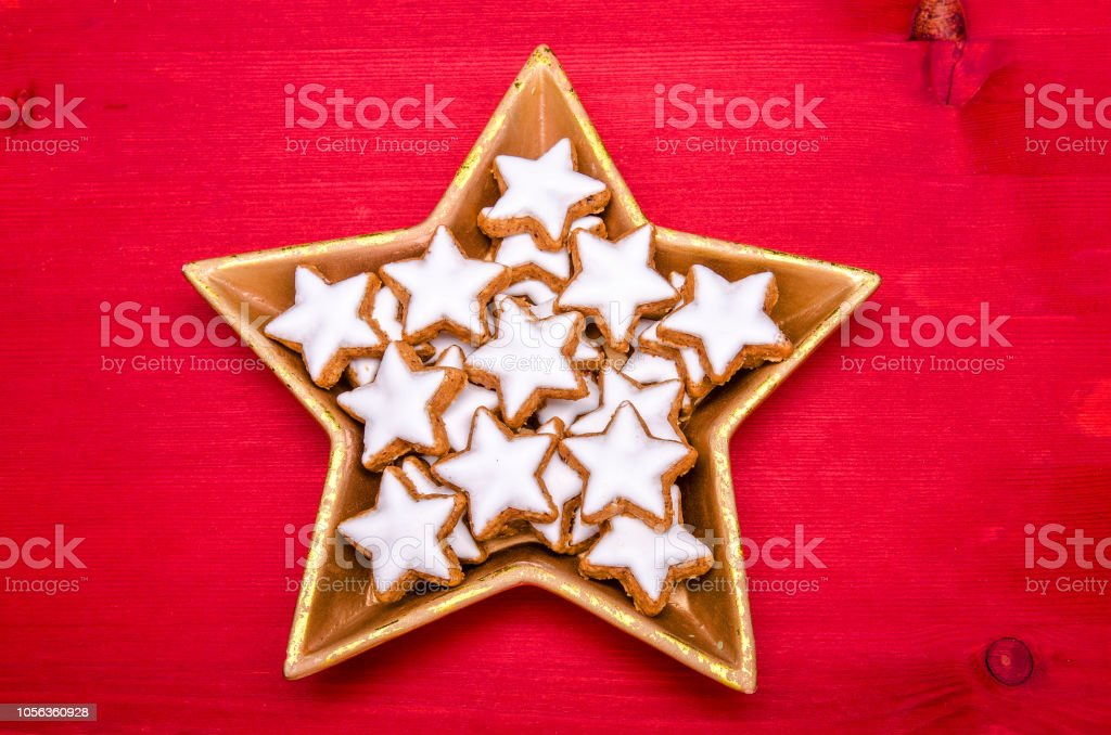 star shaped christmas cookies in a star shaped golden bowl on a red...
