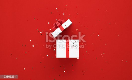 Star shaped confetti falling over white gift box tied with red ribbon on red background. Horizontal composition with copy space, Great use for Christmas and Valentine's Day related gift concepts.