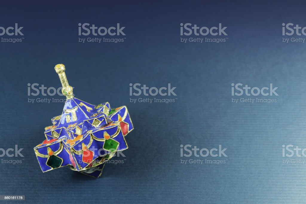 Star shaped enameled Hanukkah dreidel on a blue background with space for text stock photo