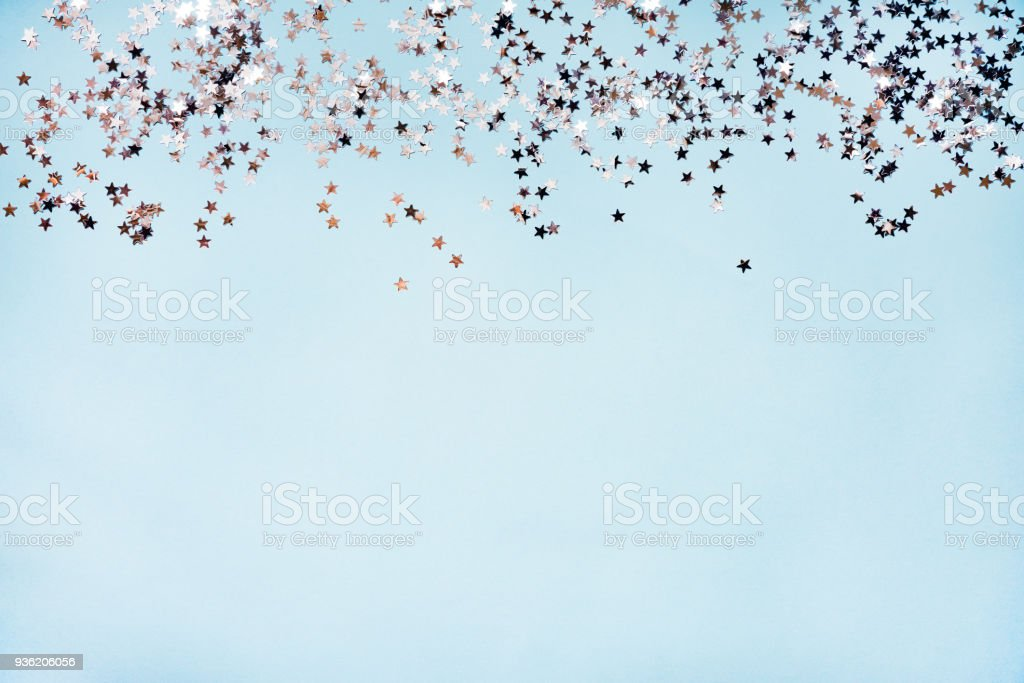Star shaped silver sequins over blue background. Copy space. stock photo