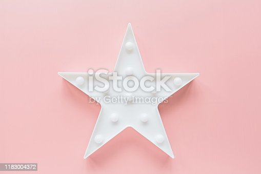 istock Star shaped white LED lights lamp single frame. Creative conceptual top view flat lay composition with copy space on pink background in minimal style. Overhead, template, mockup 1183004372