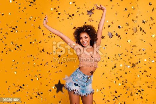 istock Star shiny sparkling rain! Concept of winning popular being the best one. Beautiful charming lovely careless  lucky woman with afro curly hair dressed in raising arms up isolated on yellow background 959591664