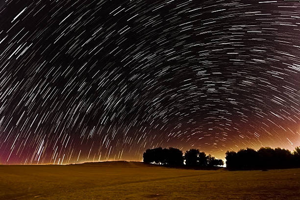Star trails and meteors over the Israel Negev desert Star trails and meteors in a very long exposure over the Israel Negev desert during the Persaid meteor shower negev stock pictures, royalty-free photos & images