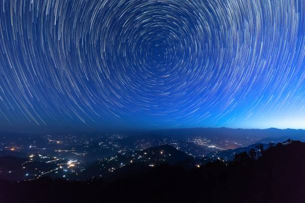 Star trails in Himalaya Night sky star trails around the North star with city lights in the background taken from the top of a hill in himalayas north star stock pictures, royalty-free photos & images