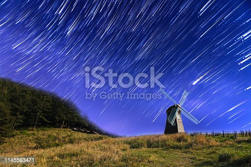 962814924 istock photo Star trails in the night over a windmill on the mountain 1145563471
