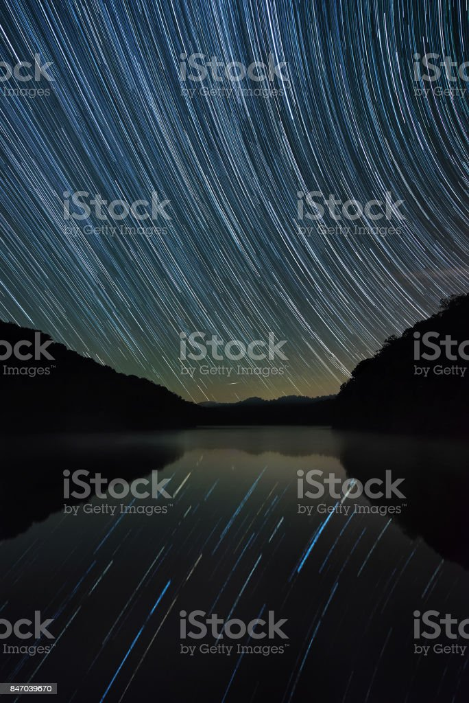 Star trails over calm mountain lake stock photo
