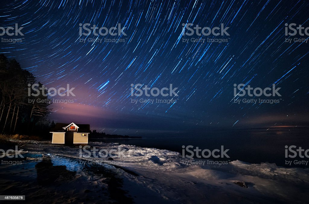 Star trails over Lake Superior at night stock photo
