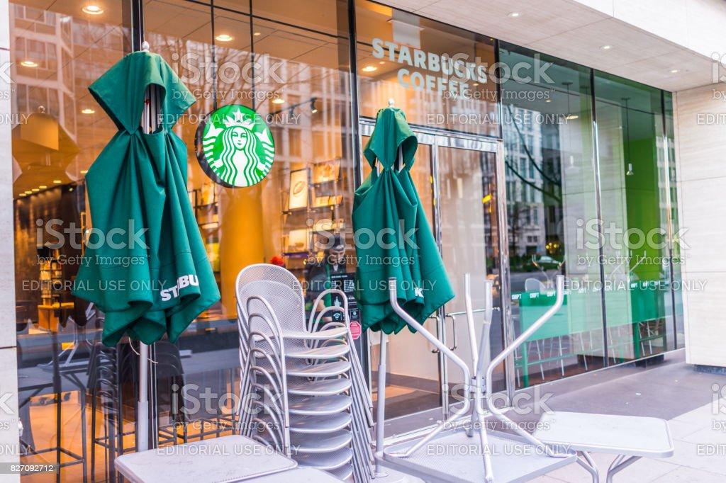 Sinal de café Starbucks e entrada com trabalhador foto de stock royalty-free