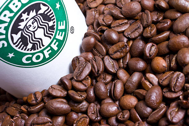 Starbucks cup with coffee beans stock photo