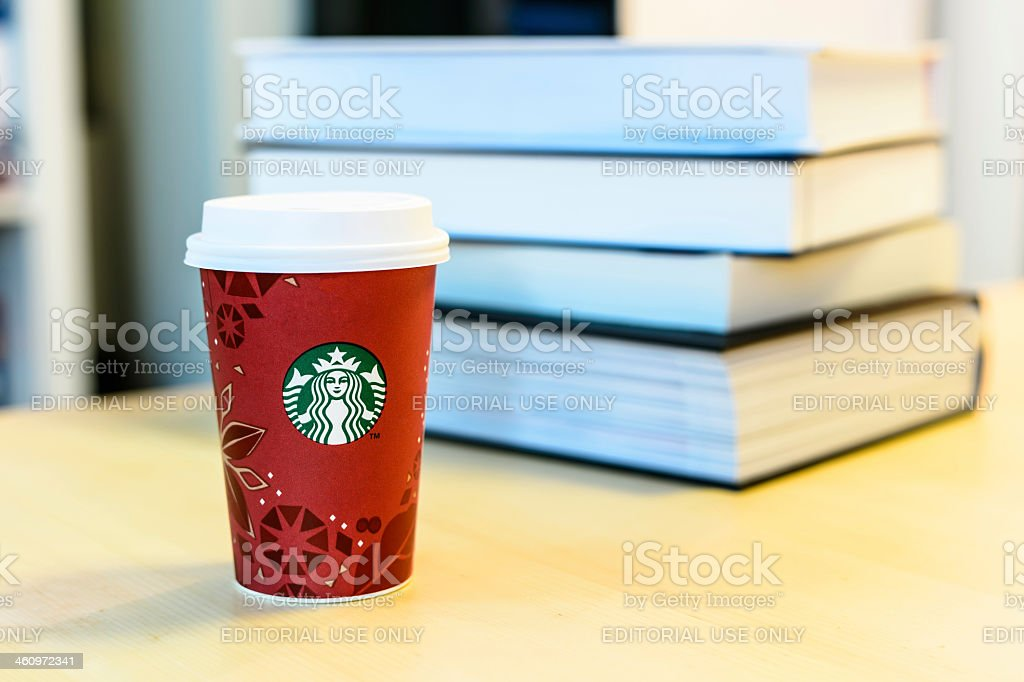 Starbucks cup with textbooks stock photo