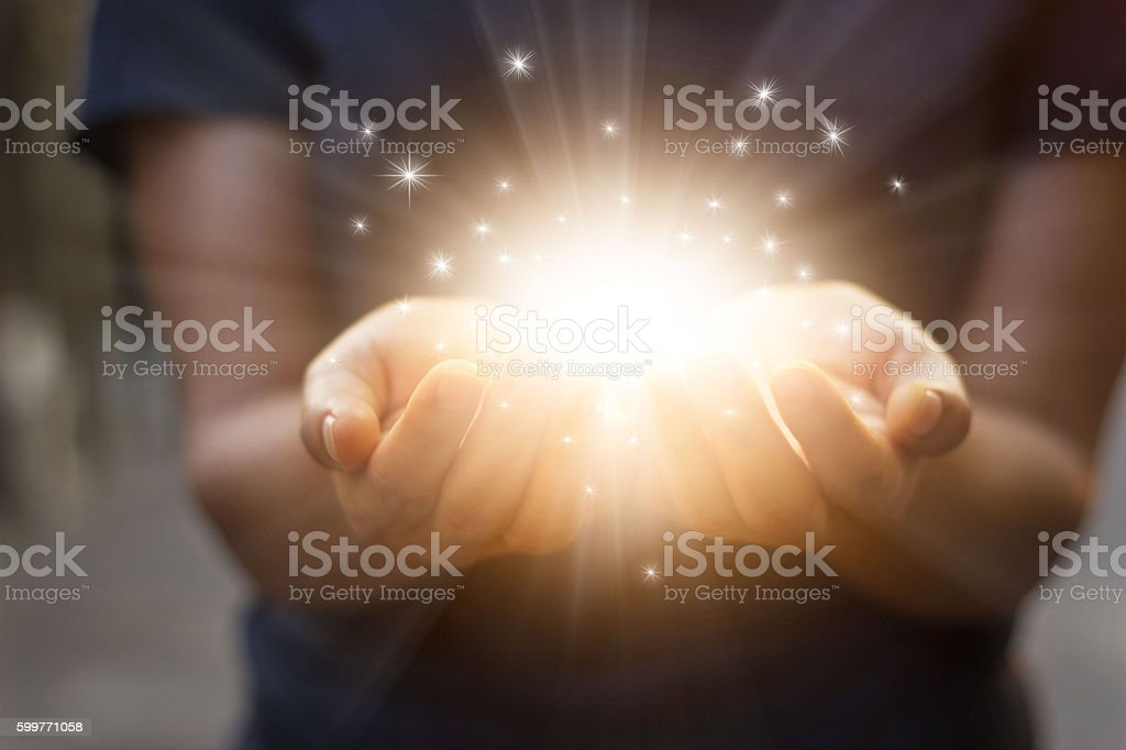 Stardust and magic in woman hands on dark background stock photo