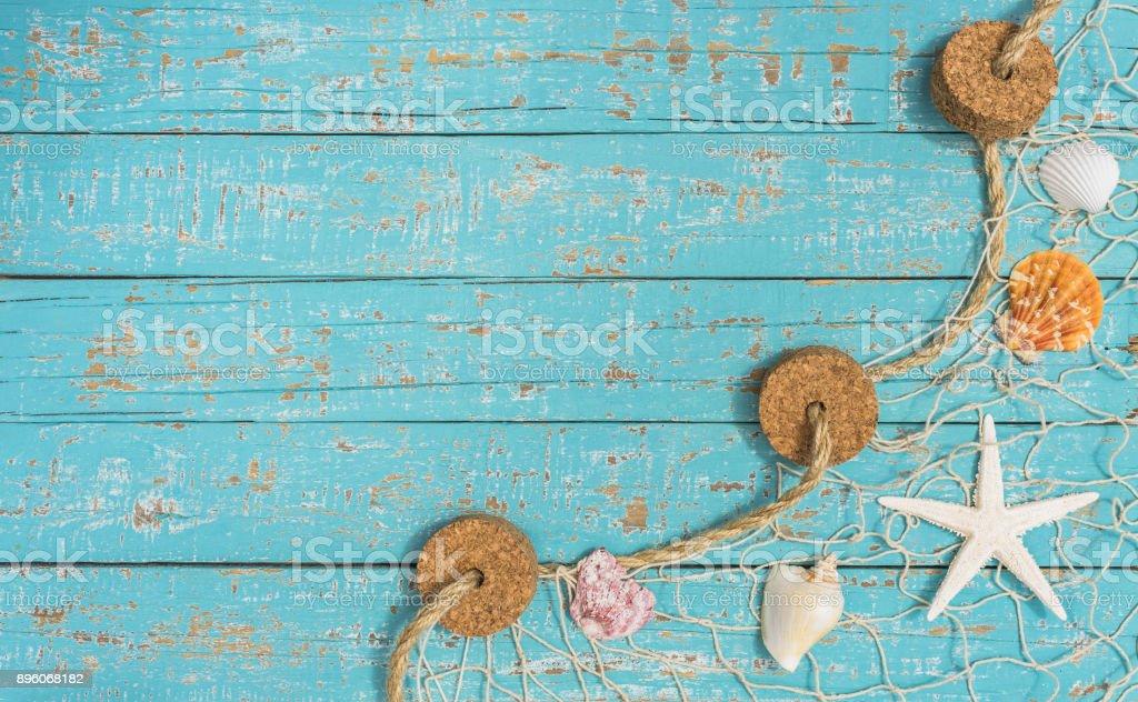 Estrela do mar e conchas em rede em turquesa fundo de madeira de pesca - foto de acervo