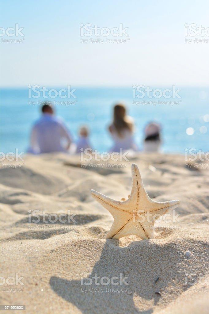 Seestern im Vordergrund als Vater und Mutter mit Kindern sitzen – Foto