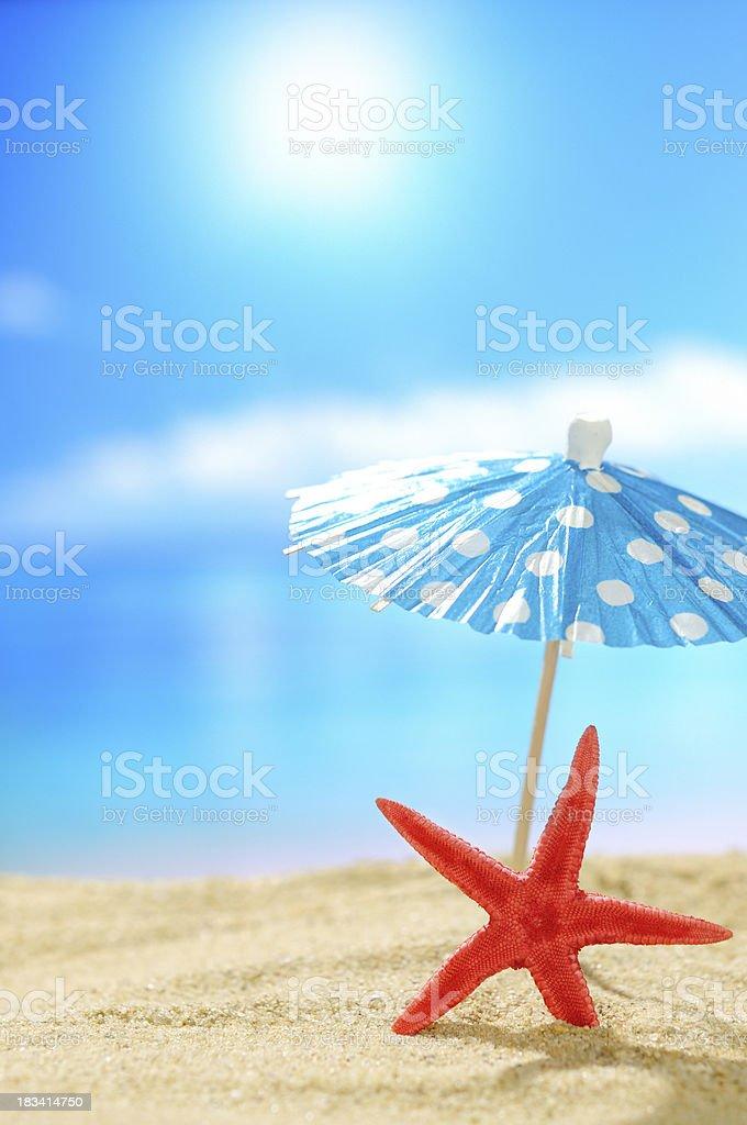 Starfish under cocktail umbrella on the beach royalty-free stock photo