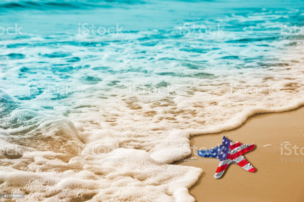 Starfish with USA flag on the sandy beach for Labor day concept stock photo