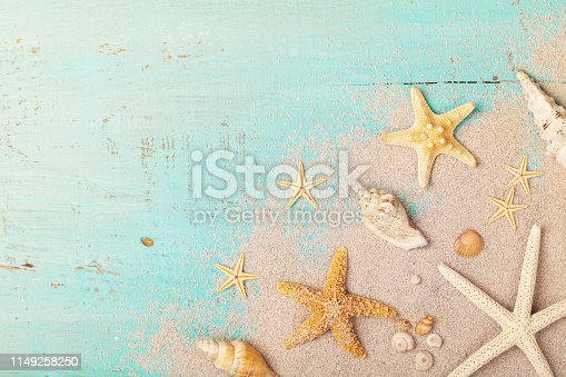 istock Starfishes and seashells on sand for summer holidays and travel background. 1149258250