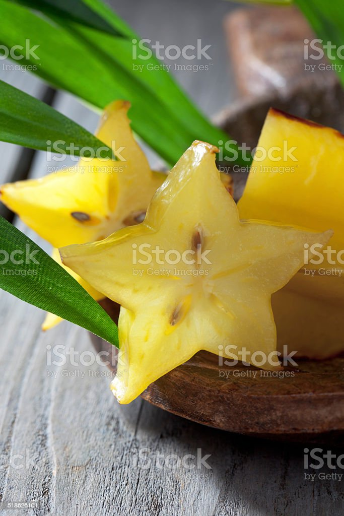 Starfruit slices on plate leaves close up stock photo