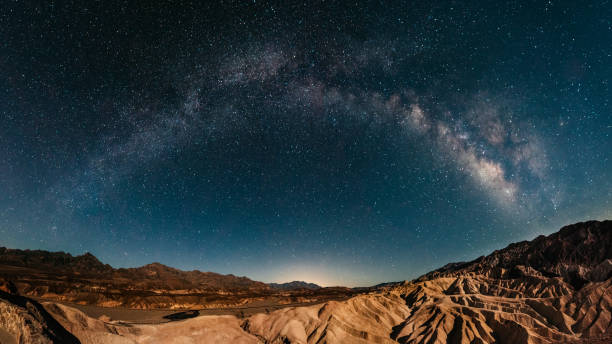 Stargazing in Death Valley Milky way raising over Zabriskie Point in Death Valley mojave desert stock pictures, royalty-free photos & images