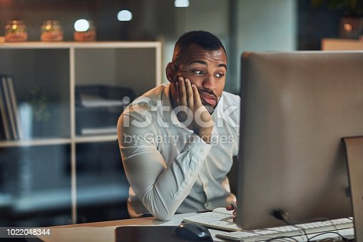 Shot of a young businessman looking bored while working at his desk during late night at work