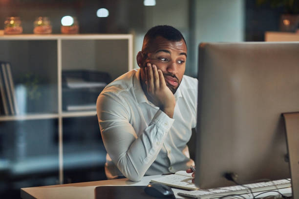 Staring at the screen but nothing's going in Shot of a young businessman looking bored while working at his desk during late night at work ambiguity stock pictures, royalty-free photos & images