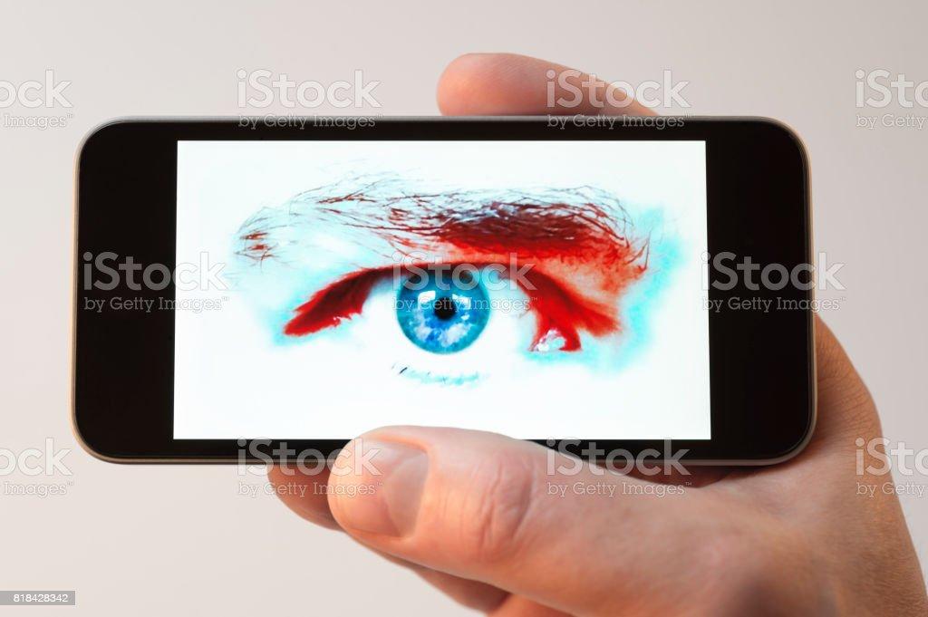 Staring eye on cellphone screen stock photo