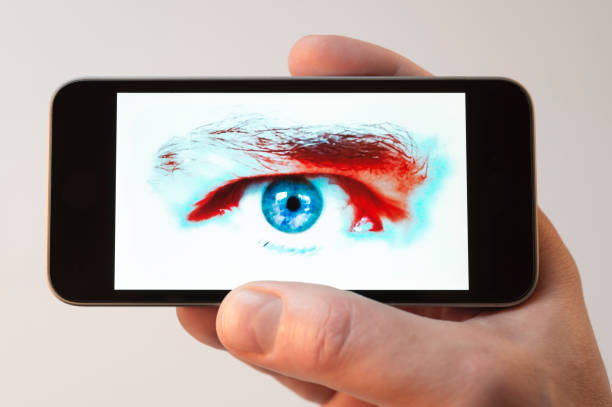 staring eye on cellphone screen - big brother orwellian concept stock pictures, royalty-free photos & images