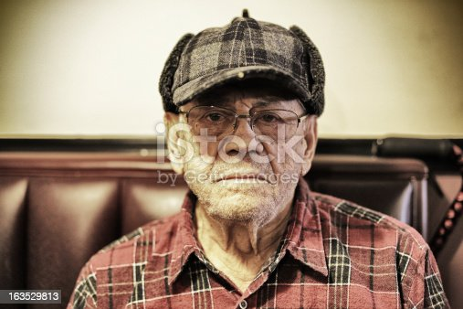 Portrait of a frowning 90 year old man sitting in a restaurant. He is dressed in a plaid hunters cap (with a tiny light on the bill) and a plaid lumberjack shirt. Desaturated toned image.