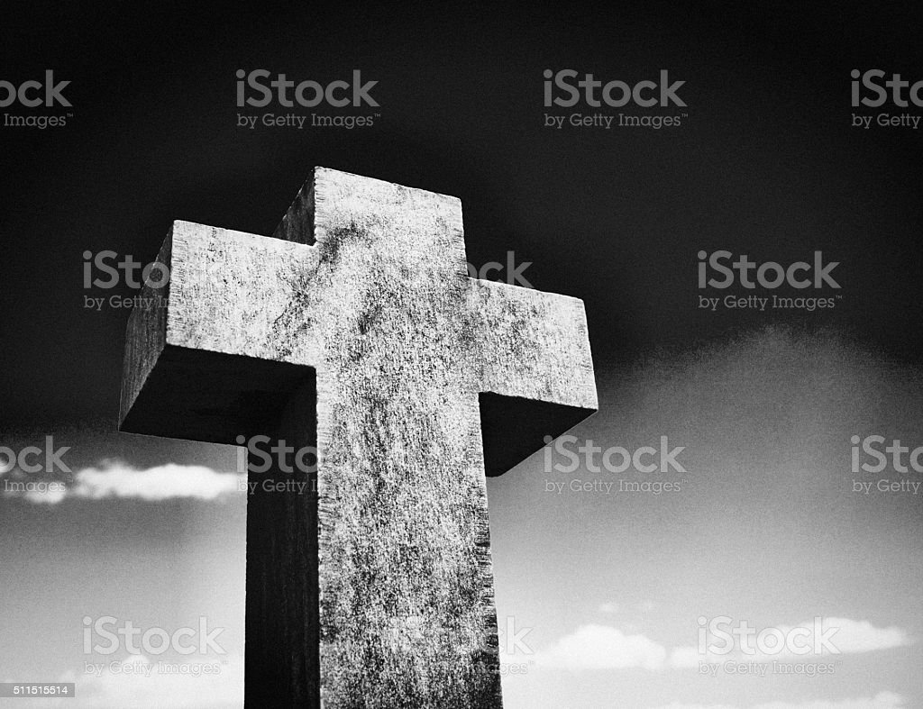 Stark stone cross against sky is a reminder of mortality stock photo