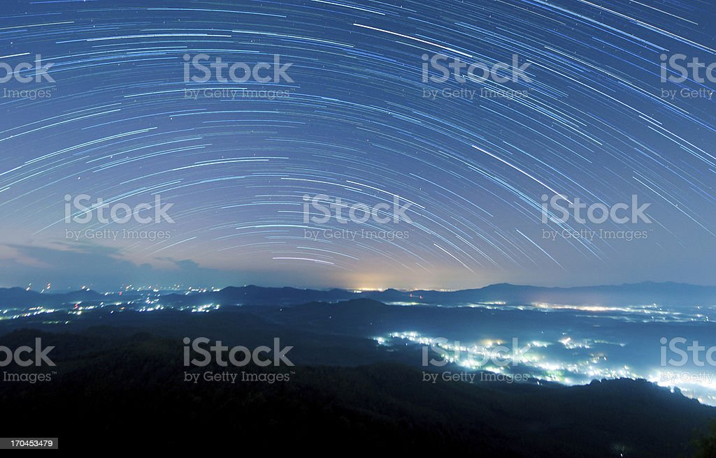 Starry night above beautiful misty mountain stock photo