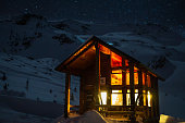 Ski touring at the Asulkan Cabin in Roger's Pass. Starry night long-exposure with an inviting hut lit up ready to welcome tired travellers.