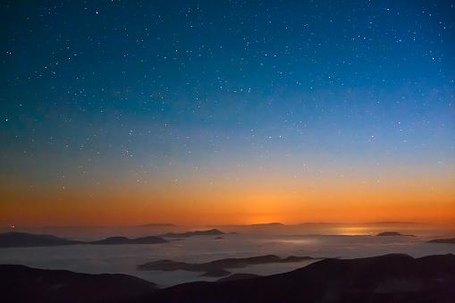 Wonderful rural scene of starry night in cloudy Carpathian Mountains