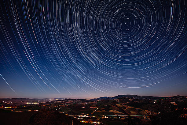 Starry Night on the Tuscan hills Beautiful track star image during a night in Tuscany. Trajectories of aircraft and shooting stars in the sky. Long exposure for trails of stars. long exposure stock pictures, royalty-free photos & images