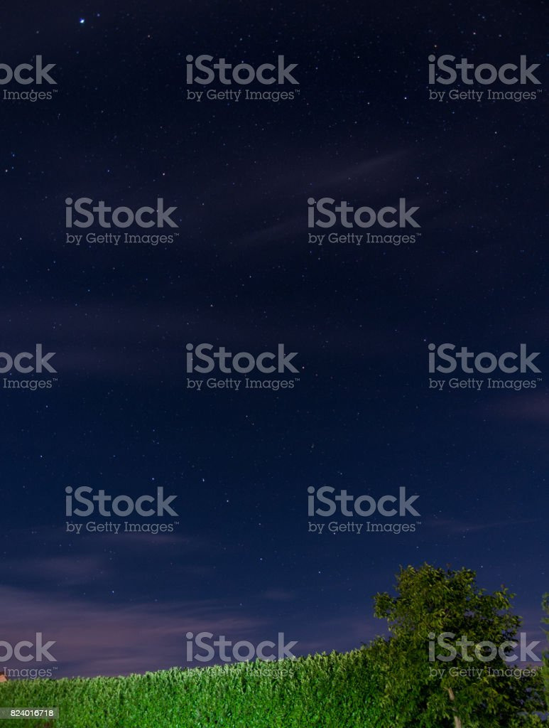 Starry night over green field in Devon, England stock photo