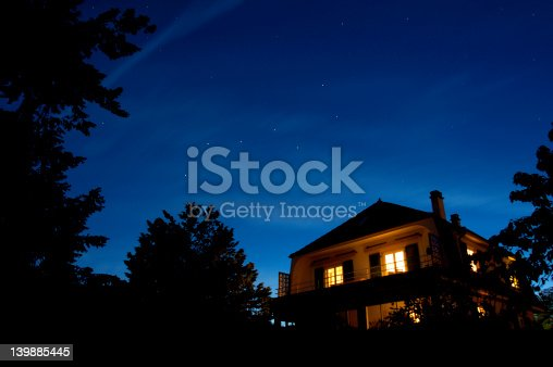 The constellation of The Plough appears in the sky as the sun sets. Other stars come out too whilst, beneath them, the lights of a house glow warmly.
