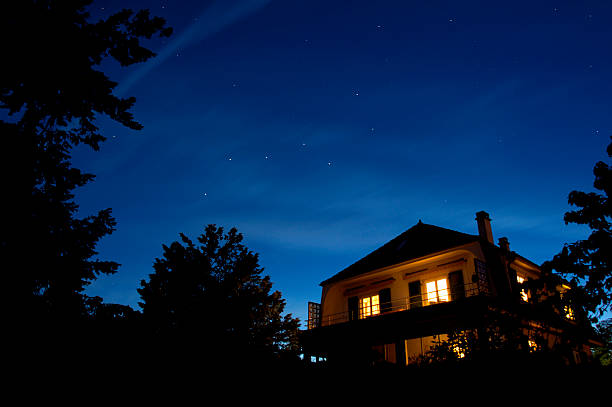 Starry night The constellation of The Plough appears in the sky as the sun sets. Other stars come out too whilst, beneath them, the lights of a house glow warmly. big dipper constellation stock pictures, royalty-free photos & images