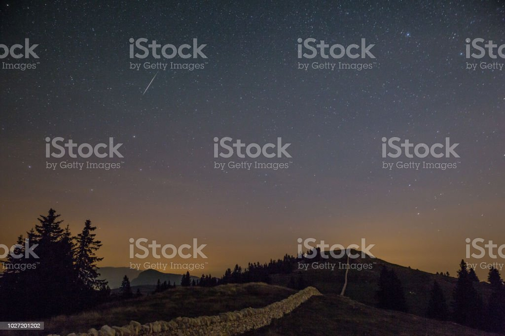 Starry Night Sky and Shooting Stars over Mountains